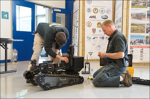Members of the Bomb Squad make adjustments to one of the robots on the Robot Test Facility floor