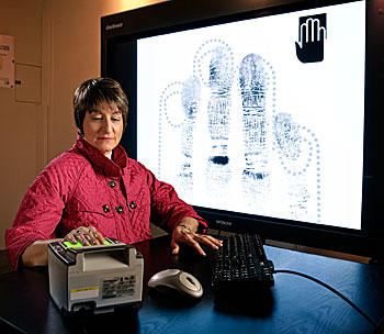 Computer scientist Mary Theofanos demonstrates a NIST-developed system that visually guides users to correctly place their hands on a digital fingerprint scanner.