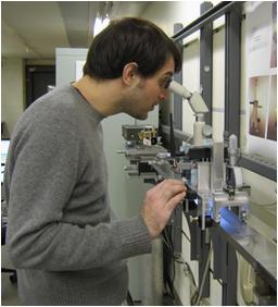 Technician measuring metal tape.