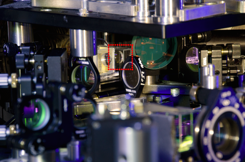 A close-up photo of the center of the experimental set-up. The small transparent chamber that holds the ultracold rubidium atoms is surrounded by a dotted line.