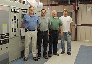 NIST engineer Matthew Deutch and technicians Douglas Sutton, Glenn Nelson, and Bill Yates (left to right) are shown with one of three WWVB transmitters as it broadcasts the station's signal in 2013.