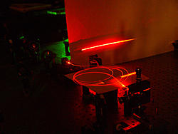 Laser light travels through an optical fiber, built at NIST, possessing a special microscopic structure that helps produce large yields of paired light particles that may be suitable for future quantum communications.