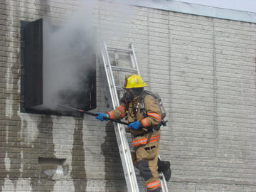 fire fighter ventilating a building