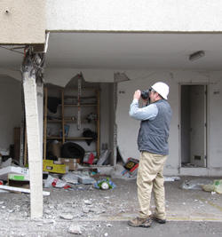 NIST researcher, Jeff Dragovich, documenting structural damage in the city of Concepcion from the 2010 Chile Earthquake.