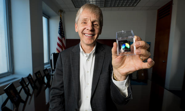 Man holding a NIST on a Chip device