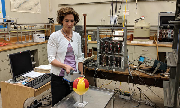 Woman standing in a lab holds a rectangular radiation detector near a metal globe that has been painted with a radiation symbol