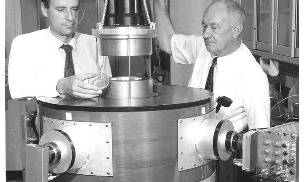 Two men stand on either side of a large cylindrical device.