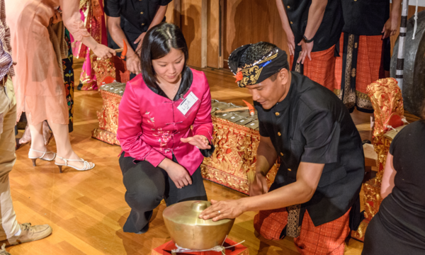 woman in a pink Asian top kneels by a ketuk along with a musician