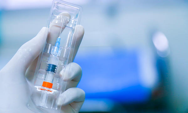 a latex gloved hand holds a syringe that has been loaded with medicine