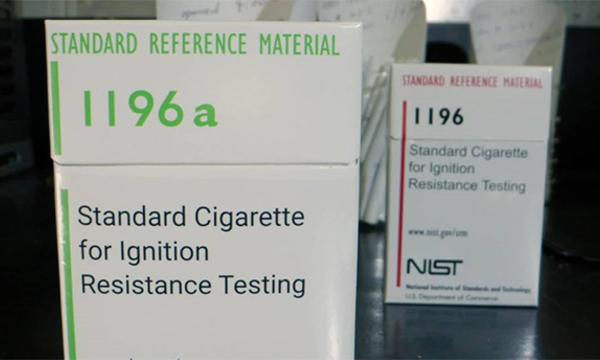 A box of cigarettes is labeled: Standard Cigarette for Ignition Resistance Testing.