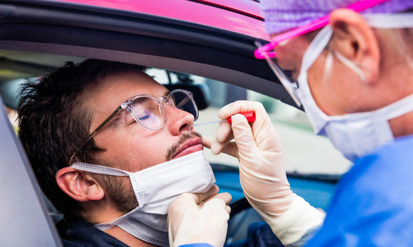 A medical worker administers a nasal swab test to a person in a car.