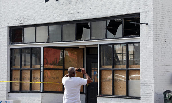 A man faces away from the camera, taking a photo of a damaged storefront.