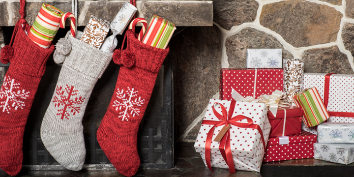 stockings stuffed with gifts hung on a fireplace mantle with wrapped presents