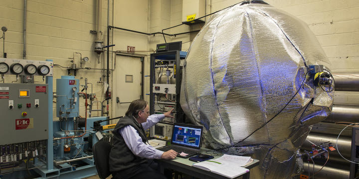 Photo of NIST scientist with the big blue ball covered in thermal insulation.