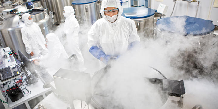 Giant metal tubs are being opened and white vapor is puffing up into the face of one researcher who is in a protective suit with hood, gloves and eye protection. In the background, several other suited researchers discuss something.
