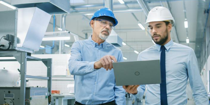 men looking at a laptop in a digital manufacturing facility