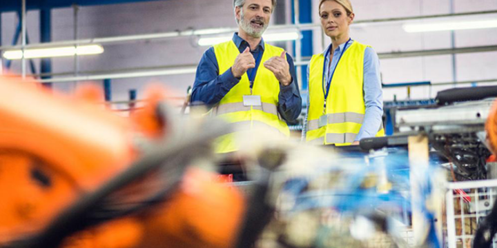 people looking at robots in action in a manufacturing facility