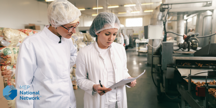 two female factory workers in a food processing plant