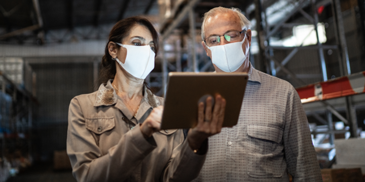 Senior partners walking and using digital tablet at warehouse with face masks