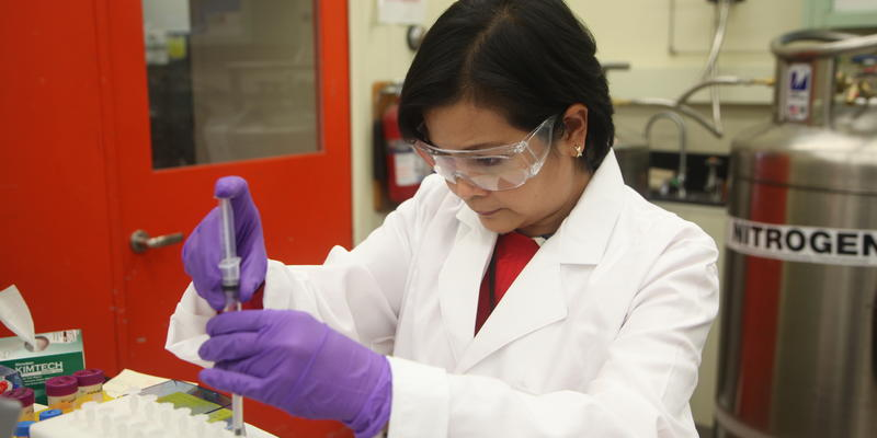 A woman with goggles prepares a sample near a large instrument.
