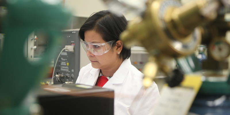 woman stands at mass spectrometer machine