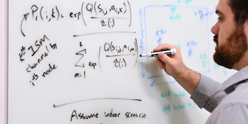 Man with dark hair writing mathematical formulas on a whiteboard on a wall.