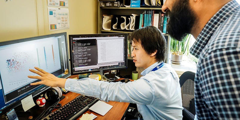 Tytus Mak sitting at his desk and while colleague Arun Moorthy and he look at a computer screen