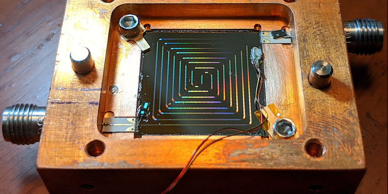 Square wood box with multicolored wires arranged in ever-smaller squares inside and three small plastic strips attached in several places.