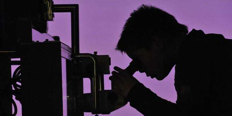 A shadow image with purple background of a male scientist looking at a microscope