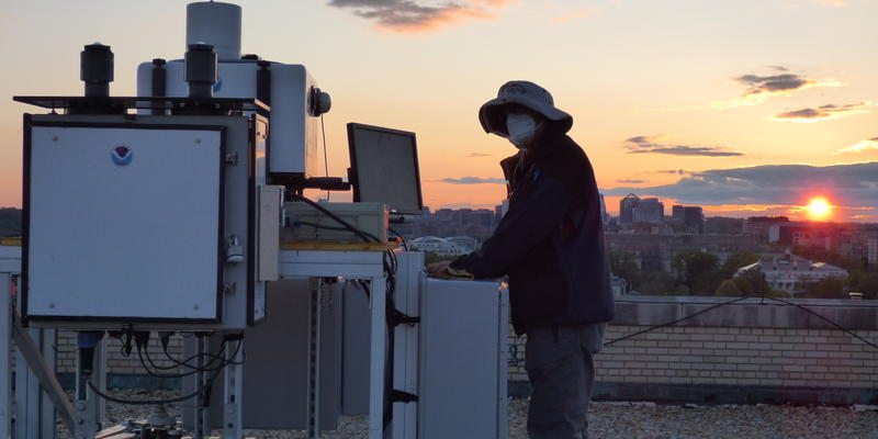 Man standing next to equipment on top of building during a sunset.