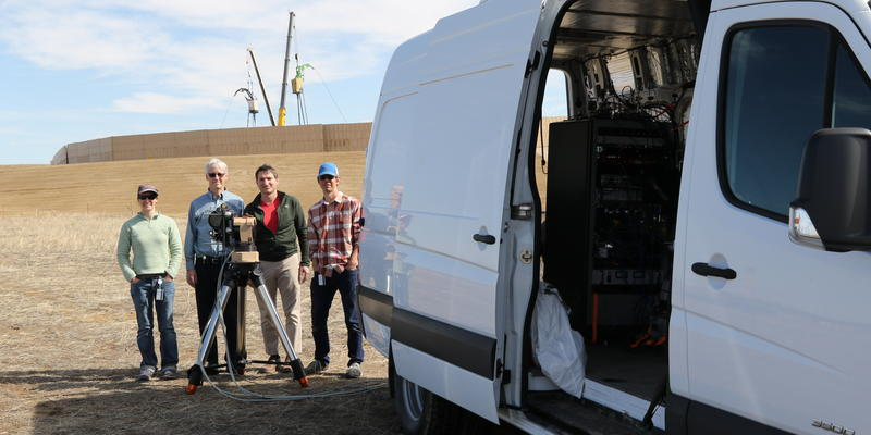 Four people stand around an instrument on a tripod next to the open door of a white van.
