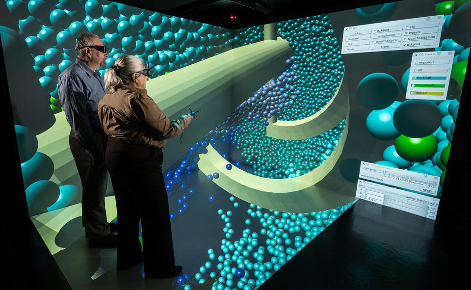 Photo of 2 researchers wearing visualization eyewear, standing in an immersive display which shows concrete particles.