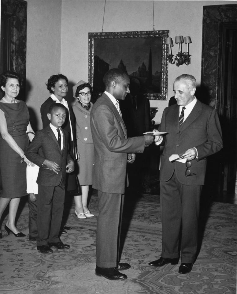 Dolphus Milligan accepting a prize from the Italian ambassador. In the background are his family members.
