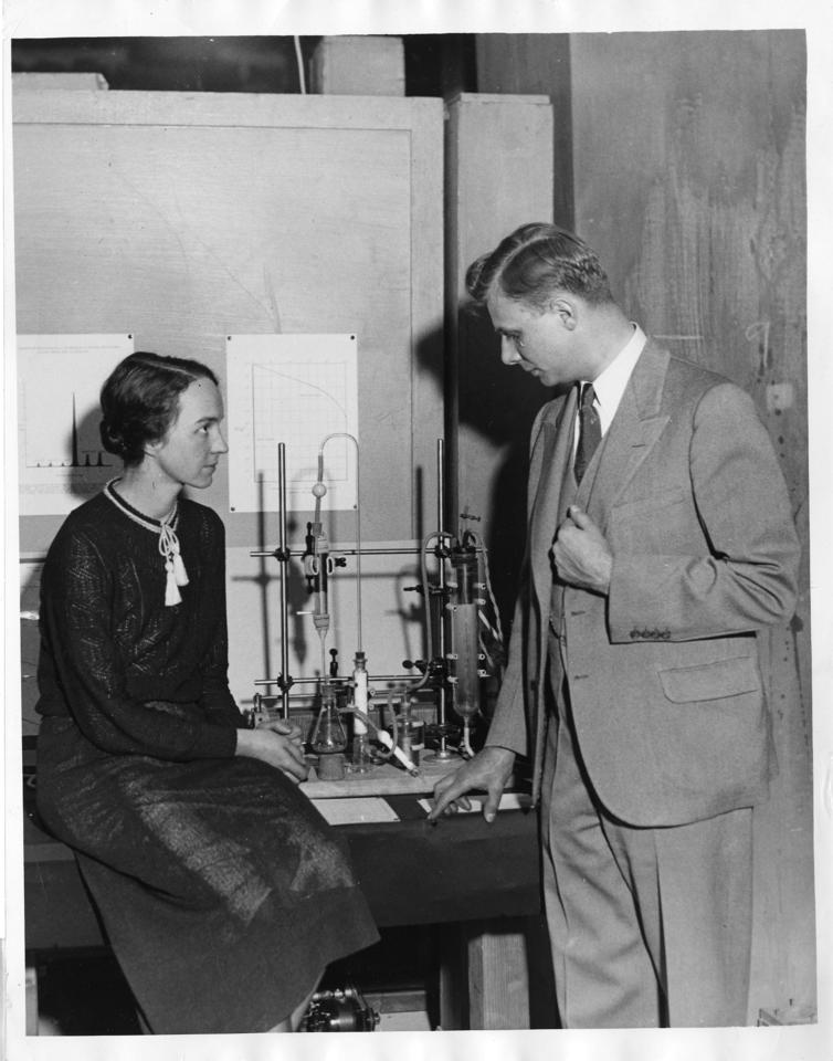 physicist Marion Langhorne Howard Brickwedde (left) and Dr. Ferdinand Brickwedde (right) with the apparatus for making heavy water between them