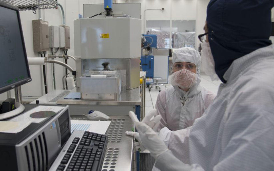 Man and woman in lab gear in front of computer screen in clean room