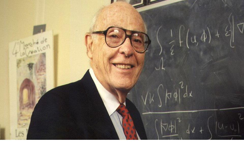 Photograph of John Cahn standing by blackboard smiling at camera