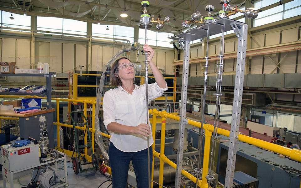 kate Ross holds a long pole used to put samples in front of a beam of neutrons  in the main hall at the NIST Center for Neutron Research.
