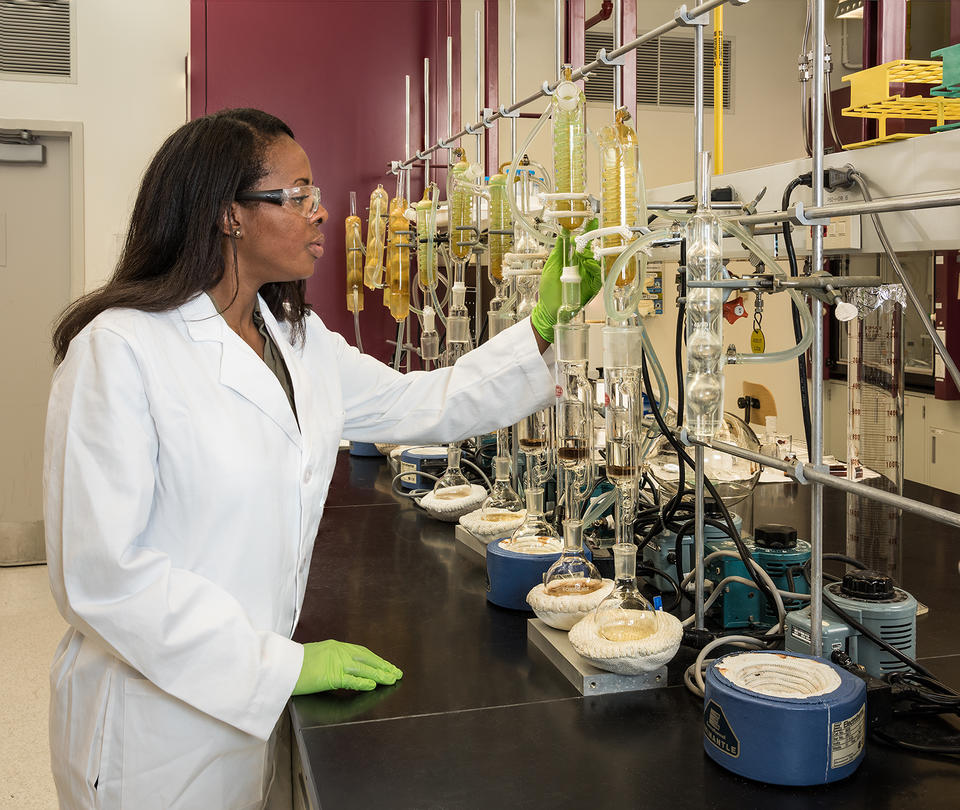A chemist stands in a white coat before a bunch of beakers.
