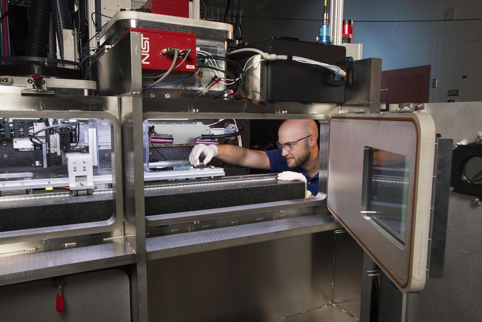 Researcher Brandon Lane making adjustments inside the large 3D printer