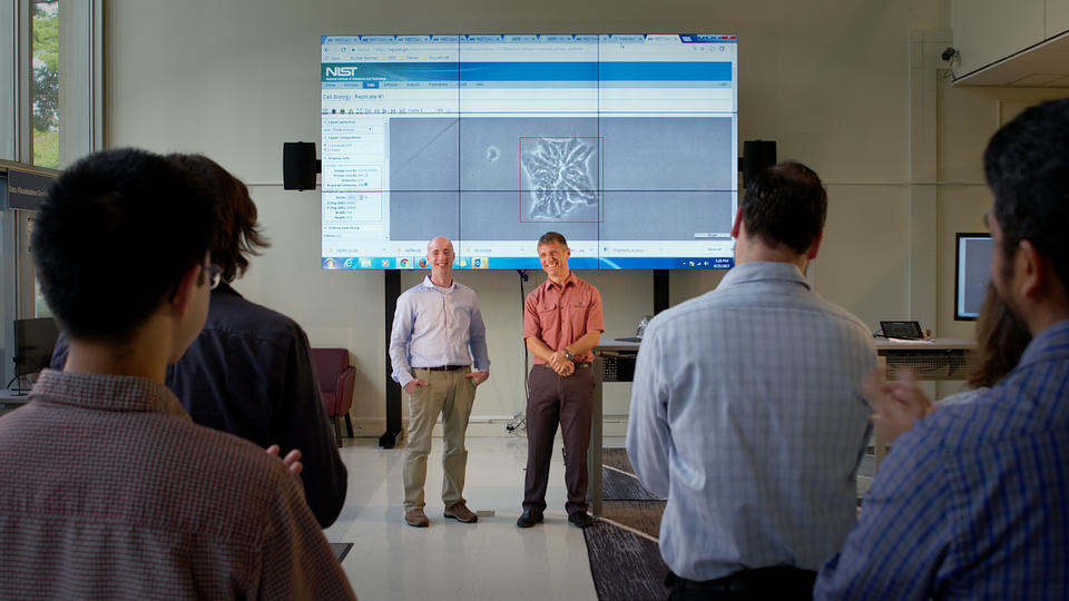 Two men stand in front of an audience, demonstrating WIPP, which is projected via computer onto several large screens in a library.