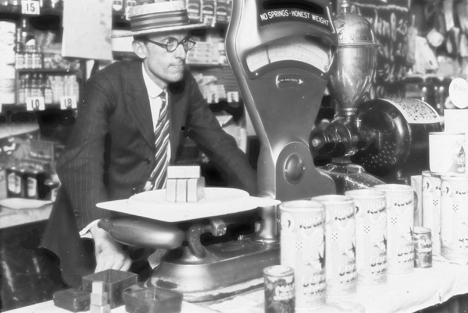 black and white photo of a 1920s weights and measures inspector checking the accuracy of a grocery store scale using test weights