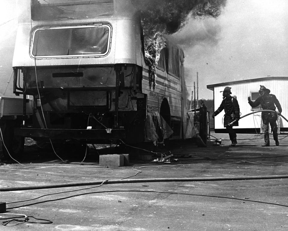 Black and white photo of bus on fire surrounded by a firemen carrying a water hose in 1975.