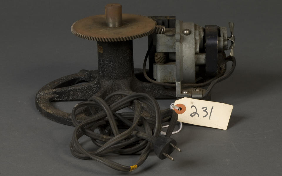 a black and bare metal motor looking device that presumably turns the gear to which it is attached