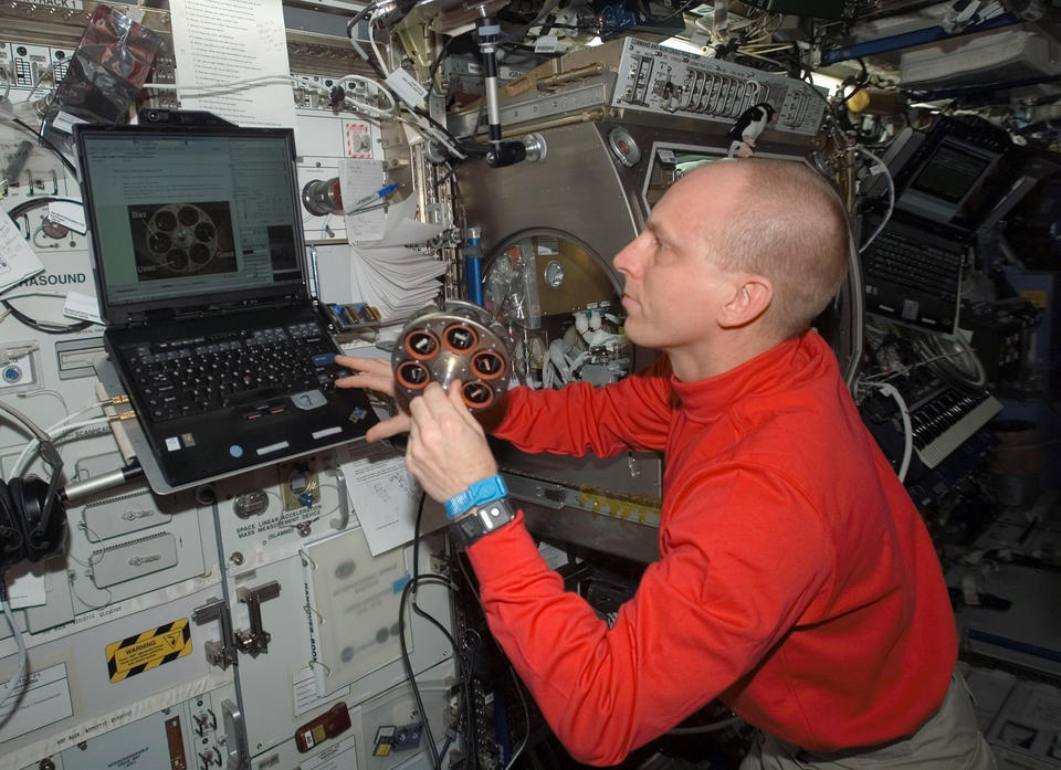 Astronaut aboard the International Space Station is seen preparing a carousel holding samples of materials for a smoke detection test.
