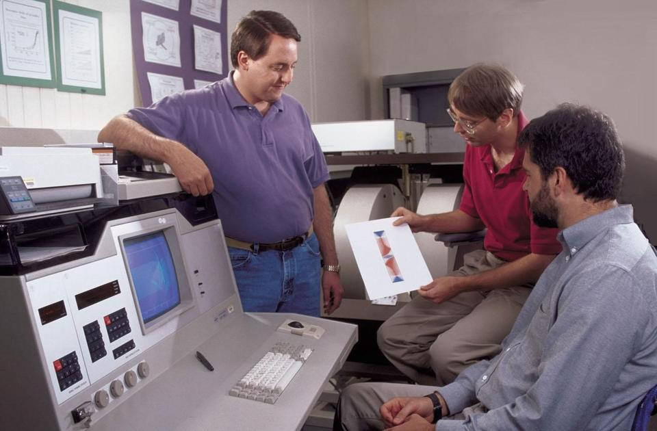 From 1998, of ACMD staff members Don Porter (left) and Mike Donahue (center) discussing micromagnetic modeling with NIST physicist Bob McMichael.
