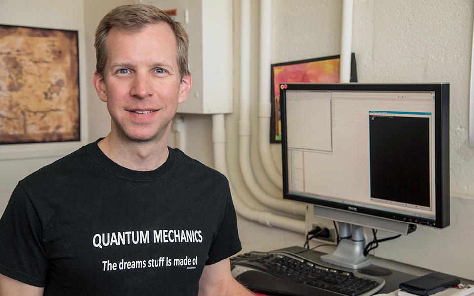 """Scott Glancy, a sandy blonde-haired Caucasian man with blue eyes, standing in his office wearing a black T-shirt that reads """"Quantum physics: The Dreams Stuff is Made of"""