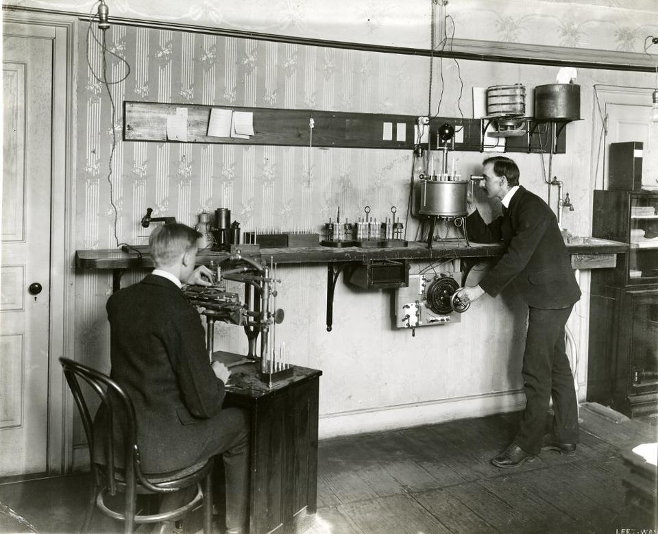 Man sits at a desk on the left while a man on the right stands looking into a device