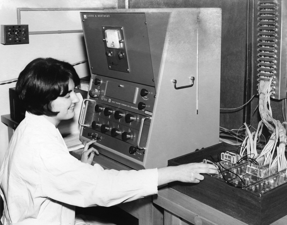 A woman in a lab coat working with electricity cells