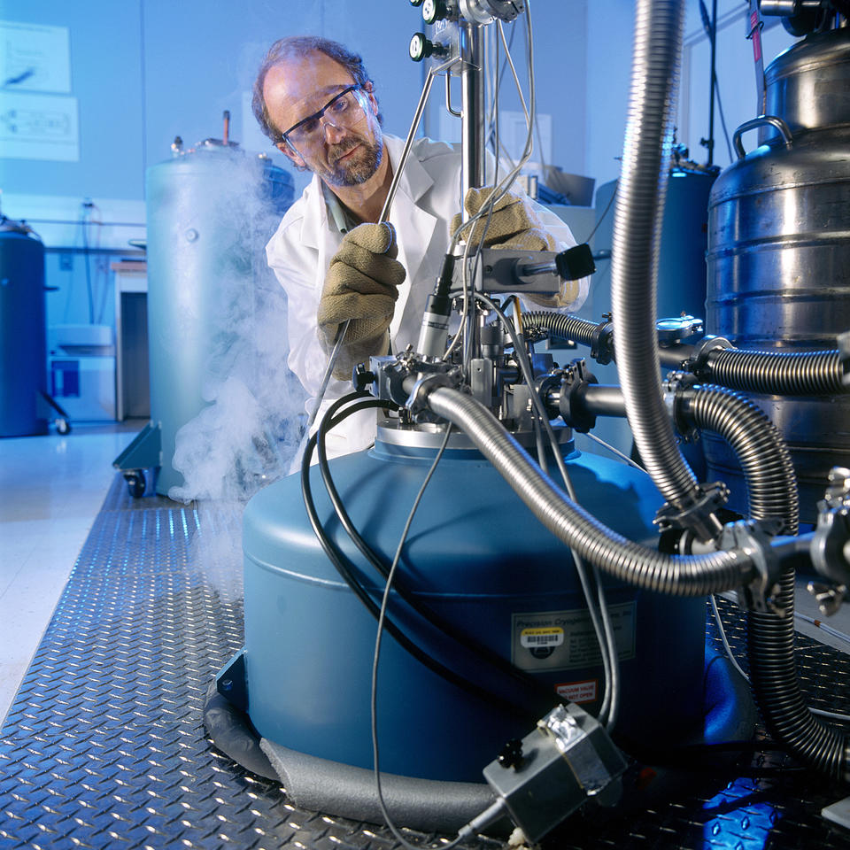 Photo of NIST physicist filling cryogenic chamber with liquid nitrogen
