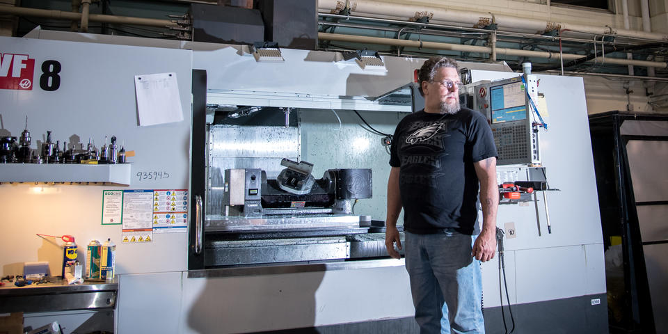 Luther Vulgamott stands in front of a five-axis computer numerical control machine